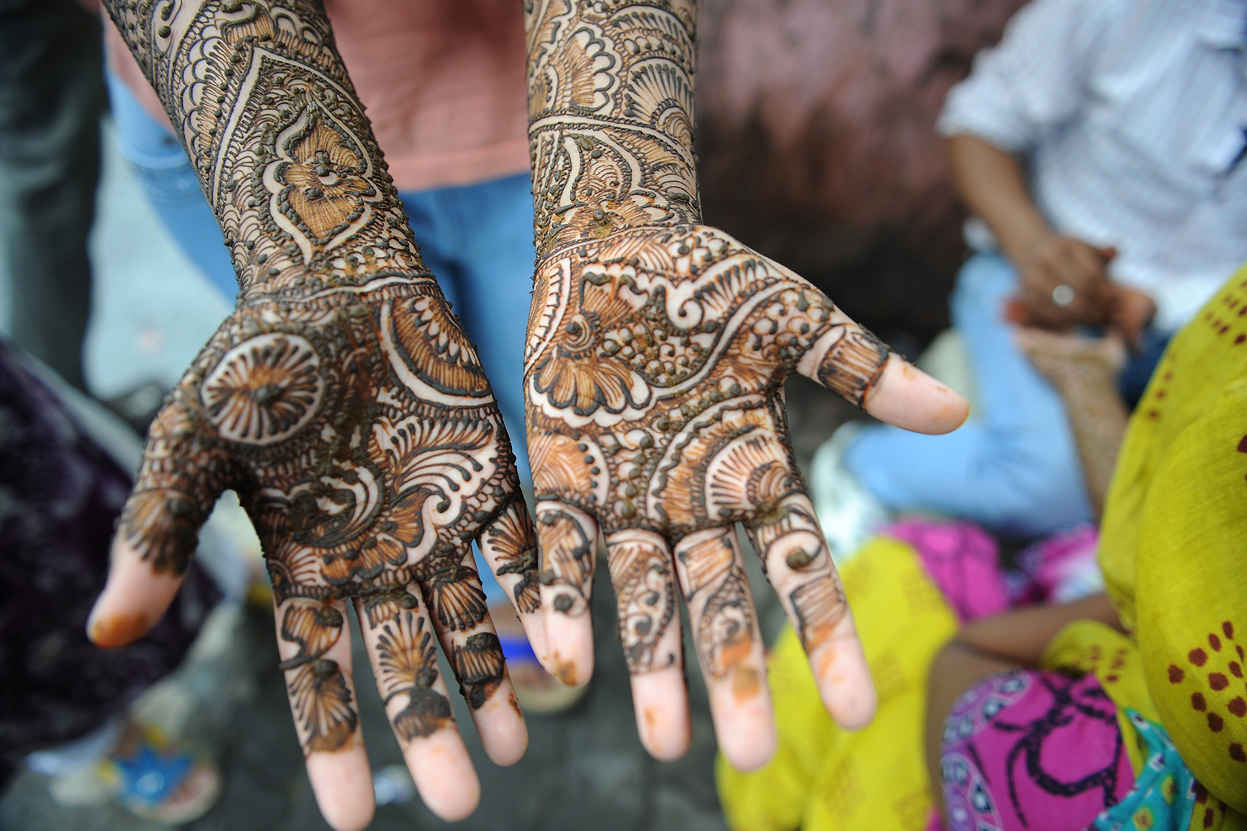 An Indian Muslim girl waits for her henna-decorated hands to dry at a roadside stall ahead of the Muslim festivities of Eid al-Fitr, in Mumbai