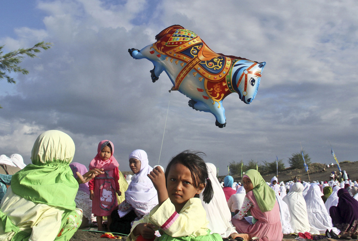 An Indonesian girl holds a balloon during Eid al-Fitr prayer