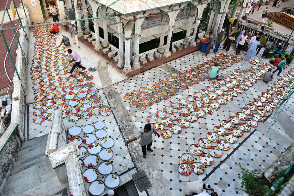 Indian Muslims lay out food for Iftar, the breaking of fast during Ramadan at the Alif Ni Masjid in Ahmedabad on July 27