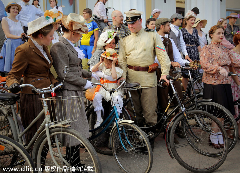 Dressed in vintage clothes, participants in St. Petersburg, Russia, ride on vintage bicycles during this year's Five Bridge Tweed Run ۴