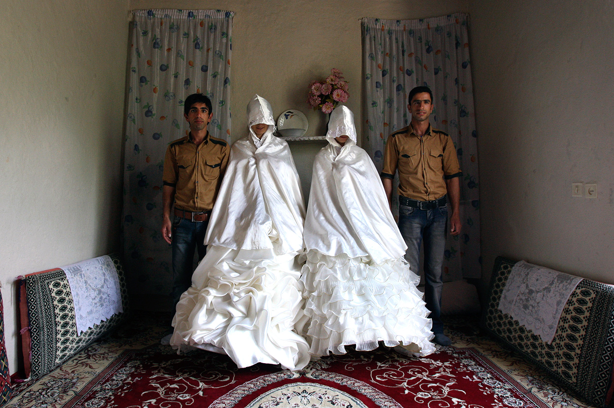 Iranian grooms, Javad Jafari, left, and his brother, Mehdi, right, pose for photographs with their brides, Maryam Sadeghi, second left, and Zahra Abolghasemi, who wear their formal wedding dresses prior to their wedding in Ghalehsar village, about 220 mi (360 km) northeast of the capital Tehran, Iran, on July 15, 2011. (AP Photo/Vahid Salemi)
