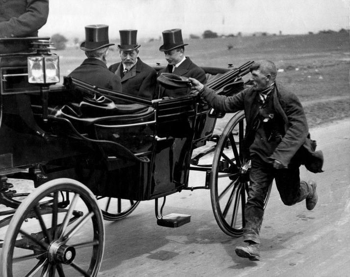 A beggar running alongside king Goarge V coach 1920