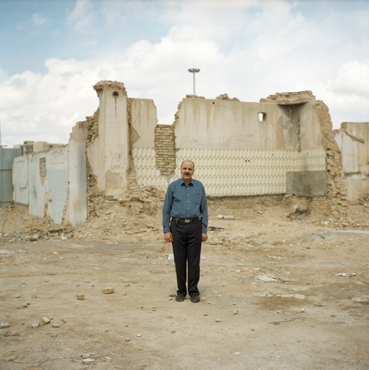 A man stands against a backdrop of ruins in Yazd.